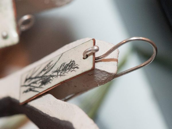 Detail of a beautiful earring showing the hand drawn surface.