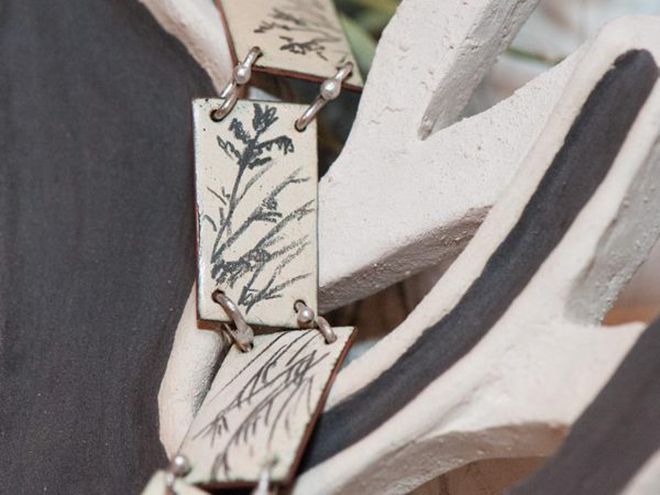 Detail of the links of the bracelet showing the intricate drawings on each.